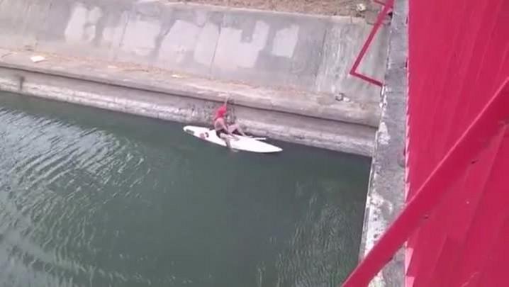 Homem surfa em prancha de Stand Up Paddle no Arroio Dilúvio