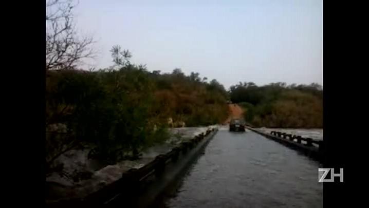 Motoristas se arriscam e atravessam ponte tomada pela água