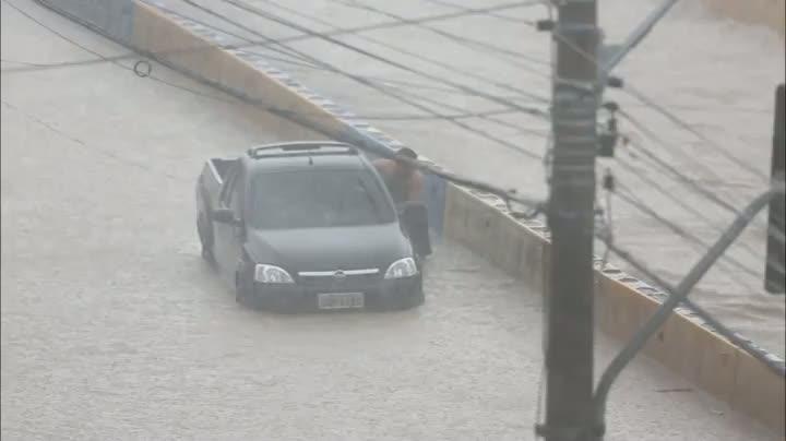 Motorista empurra carro apagado em avenida que virou rio