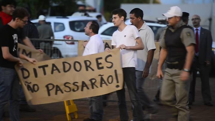 Manifestantes posicionam cartazes em frente a cemitério de São Borja onde o corpo de Jango será exumado