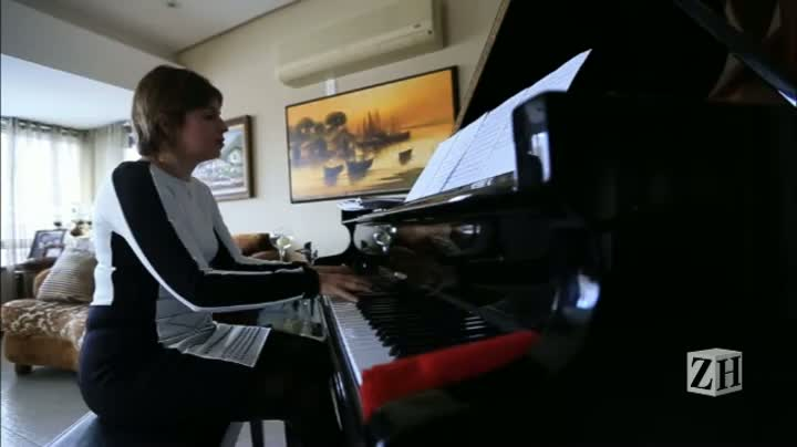 Cynthia Geyer, diretora da escola de música e artes Estação Musical, toca piano em casa
