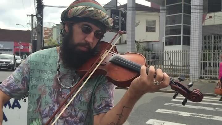 Homem que deseja viajar 25 países com seu violino passa por Joinville