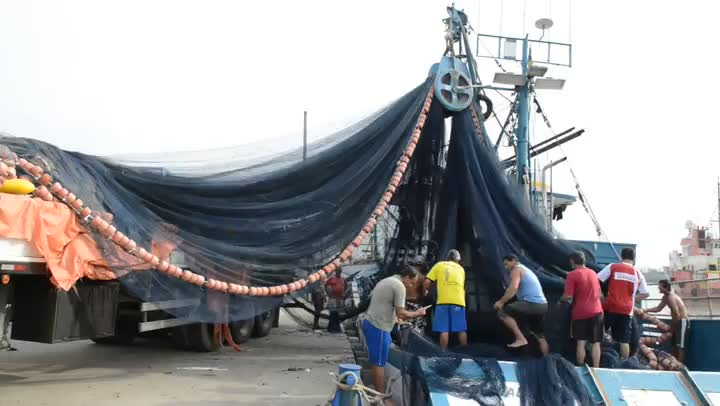 Pescadores preparam barco para pesca de tainha