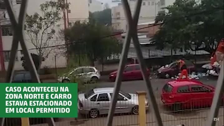 Garis jogam lixo em cima de carro estacionado