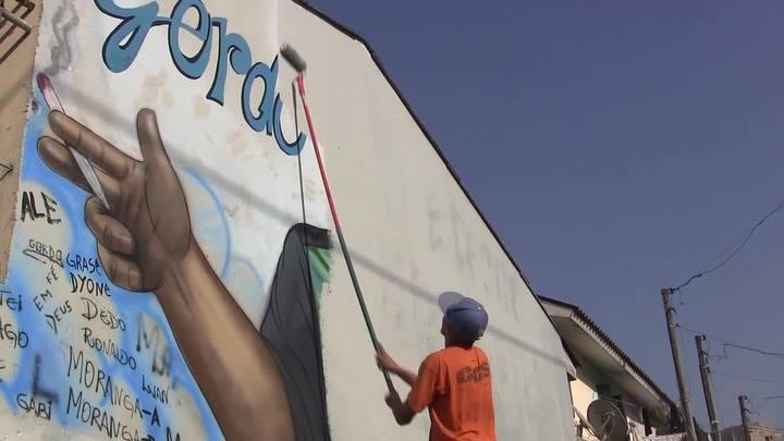 Polícia pinta muro com imagem de traficante