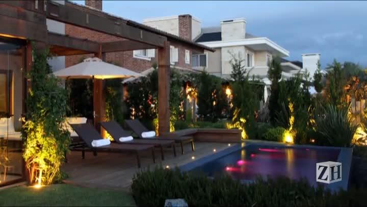 Iluminação pontual no jardim e dentro da piscina dá vida a projeto paisagístico de casa na praia