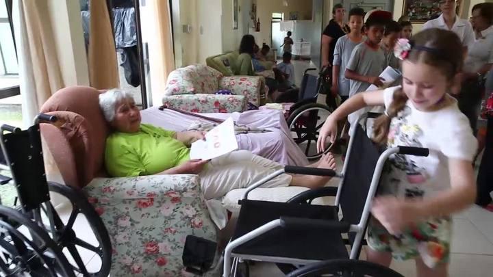 Betina entrega cadeiras de rodas a idosos